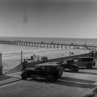 Image: View of jetty and beach with automobiles in the foreground in a parking lot.