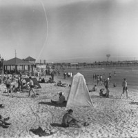 Image: People on a beach with a jetty in the background