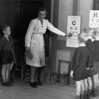 Image: woman showing children eye chart