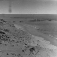 Image: High sand dunes with a jetty in the background