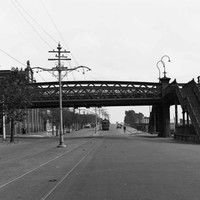 Image: two flights of stairs lead up to a metal bridge which passes over a wide paved road upon which an electric tram travels