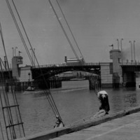 Image: A drawbridge within an active port is closed after a small boat has passed beneath it. A wharf with two mid-twentieth century sailing vessels tied alongside it is visible in the immediate foreground