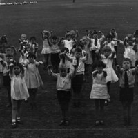 Image: large group of children on oval with arms stretched forwards