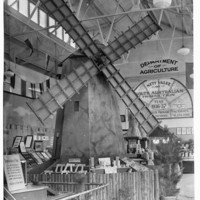 Image: A windmill is on display inside of a tall building.  There is a sign in the background that reads: Department of Agriculture
