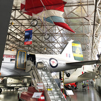 Image: group of planes in large hanger style building with flag draped from ceiling