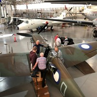 Image: group of planes in large hanger style building with people on platforms climbing into plane