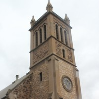 Image: the front entrance of a stone church with a single square tower with a clock.