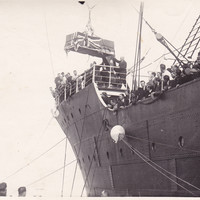 Image: casket being unloaded by crane from a ship