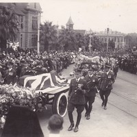 Sir Ross Smith's flag-draped casket passes by as mourners look on