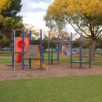 Image: Playground equipment sits in the middle of an open park interspersed with trees of different species