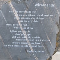 Image: A rough stone monument with text inscribed on a single polished flat face. The text is a poem entitled 'Wirranendi'