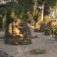 Image: Five large dome-shaped stone structures in a gravel-filled garden bed sit next to a busy road.
