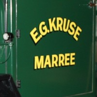 Image: A robust 1930s-era flat-bed truck on display at a museum. The words 'E.G. Kruse, Marree' are stencilled on the passenger door