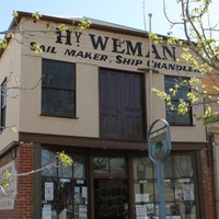 Image: A two-storey building with brick first floor and corrugated metal second floor. The words 'Hy. Weman, Sail Maker, Ship Chandler' are painted on the building shop front