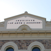 Image: A large, two-storey stone building with the words 'Institute of Arts & Sciences' painted on its front façade