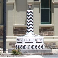 Image: A large plinth painted with an alternating black and white pattern, and emblazoned with the words 'Keep Left' and directional arrows at its base. It is displayed on a street corner in front of a large stone Victorian building with corner tower