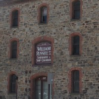 Image: A large, three-storey nineteenth century stone warehouse located next to a paved road. A sign in one of the windows reads 'Est 1870, William Russell Pty Ltd., Sailmaker & Ship Chandler'