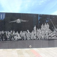 Wall with illustrations of men and machines displayed on it