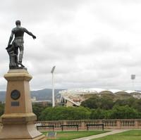 Image: Bronze statue of man pointing over stadium