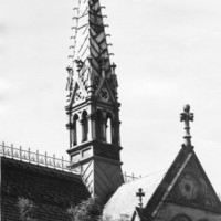 Image: a square gothic style open tower with a very steeply pitched roof rises from the centre of a crossed gable roof