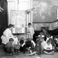 Image: a caucasian woman sits on a stool surrounded by children in a classroom with blackboards on the walls