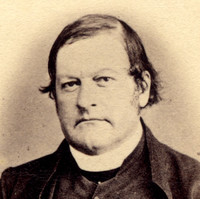 Image: A photographic head-and-shoulders portrait of a Caucasian man in Victorian-era priest's attire