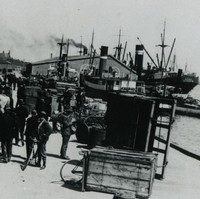 Image: A group of men mill about on a wharf. Two steamships are visible in the background. What appears to be a horse-drawn cart tipped on its side is located at the edge of the wharf