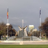 Image: a large fountain made of granite and aluminium featuring seated figures with birds and flanked by two flagpoles flying the Australian and Indigenous flags.