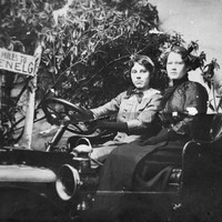 Image: two women pose for photograph in a motor car