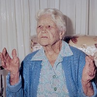 Image: elderly caucasian woman holds up her hands as she retells a story