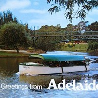 "Image: a postcard with the greeting ""Greetings from Adelaide"". The image is of a small blue and white boat with a covered seating area sailing down a wide river which winds through parklands. In the background is a green metal footbridge."