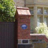 Image: Old stone building with blue plaque on the brick wall outside
