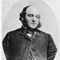 Image: Portrait photograph of a man in an oval frame wearing a jacket and holding a walking stick