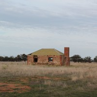 Image: Colour photo of an abandoned brick building in a field.