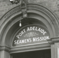 Image: Four Caucasian men in early twentieth century attire stand outside the front entrance of a large bluestone building. A sign above the entrance door reads 'Port Adelaide Seamen's Mission'