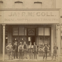 Image: A group of Caucasian men in late nineteenth-century labourer attire stand in front of a shop. The words 'Jas. R. McColl, House and Ship Plumber, Tinsmith, &c.' are painted on the front of the building