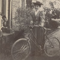 Image: a woman standing beside a bicycle at the side of a stone building
