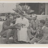 Image: A woman and three men sitting in a garden