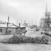 Image: Several late nineteenth century sailing ships are moored alongside a large wharf in a port town. A large pile of stone ballast and rail cars are visible in the foreground, while a single-storey bluestone building is located nearby