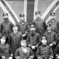 Image: A group of men attired in nineteenth-century South Australian customs service uniforms pose for a photograph. A large Union Jack flag appears as a backdrop behind the men