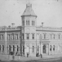 Image: A large, two-storey stone building in Victorian Italianate style. It features a large, octagonal tower with an additional storey in one corner. A group of men in nineteenth century attire congregate in front of the building