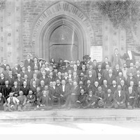 Image: crowd of congregation sitting in front of church facade and doorway