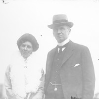 Image: man wearing hat and woman with boa pose for photograph