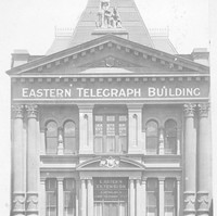 "Image: Photograph of the front of a building. It has several columns and reads ""Eastern Telegraph Building"""