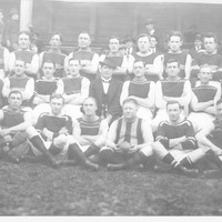 Image: A uniformed sports team poses for a photograph. A man in suit and hat sits in the centre of the group