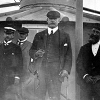 Image: A group of middle-aged Caucasian men in early Edwardian attire pose for a photograph outside a metal lighthouse. One man is wearing what appears to be a government uniform