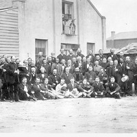 Image: Black and white photograph of men at rear exterior of a building