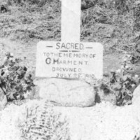 Image: Two middle-aged Caucasian men in Edwardian attire flank a simple grave site. The grave is covered with stone and features a large white wooden cross, to which is attached a sign that reads 'Sacred to the memory of G. Marment, drowned July 28 1910'
