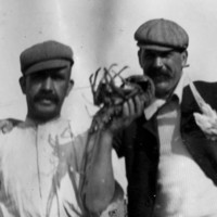 Image: Two young moustachioed Caucasian men in Edwardian-era work clothing pose for a photograph. The men stand in front of a cottage and white picket fence, and the man on the left holds a large crayfish in his left hand