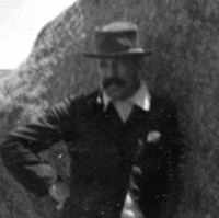 Image: A young moustachioed Caucasian man in casual early Edwardian attire poses for a photograph next to a large rock formation on an island